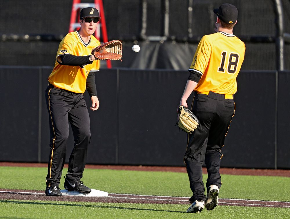 Iowa Hawkeyes first baseman Connor McCaffery (30) pulls in a toss from pitcher Shane Ritter (18) for an out during the sixth inning of their game at Duane Banks Field in Iowa City on Tuesday, Apr. 2, 2019. (Stephen Mally/hawkeyesports.com)