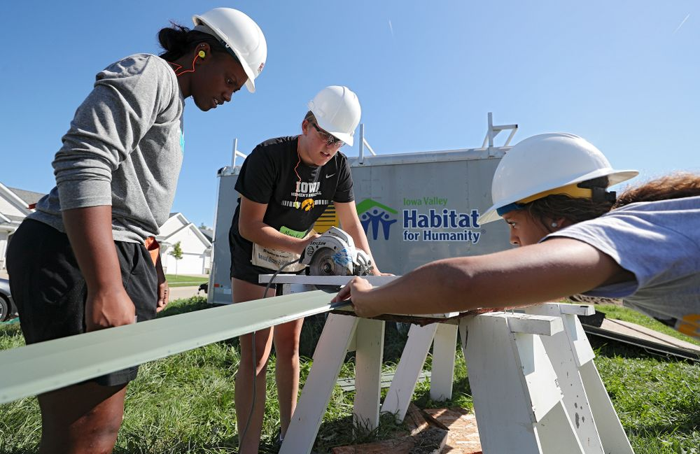 Iowa's Zion Sanders (from left), Monika Czinano, and Gabbie Marshall work on cutting a piece of siding as they work on a Habitat for Humanity Women Build project in Iowa City on Wednesday, Sep 25, 2019. (Stephen Mally/hawkeyesports.com)