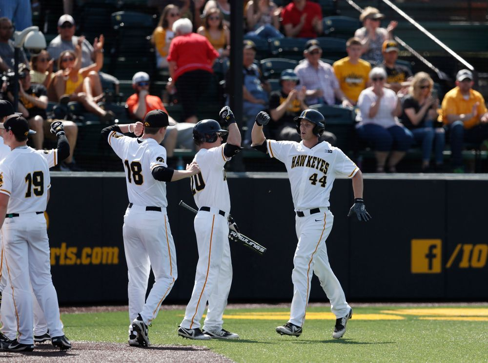Iowa Hawkeyes outfielder Robert Neustrom (44) celebrates with catcher Austin Guzzo (20) after scoring against the Oklahoma State Cowboys Saturday, May 5, 2018 at Duane Banks Field. (Brian Ray/hawkeyesports.com)