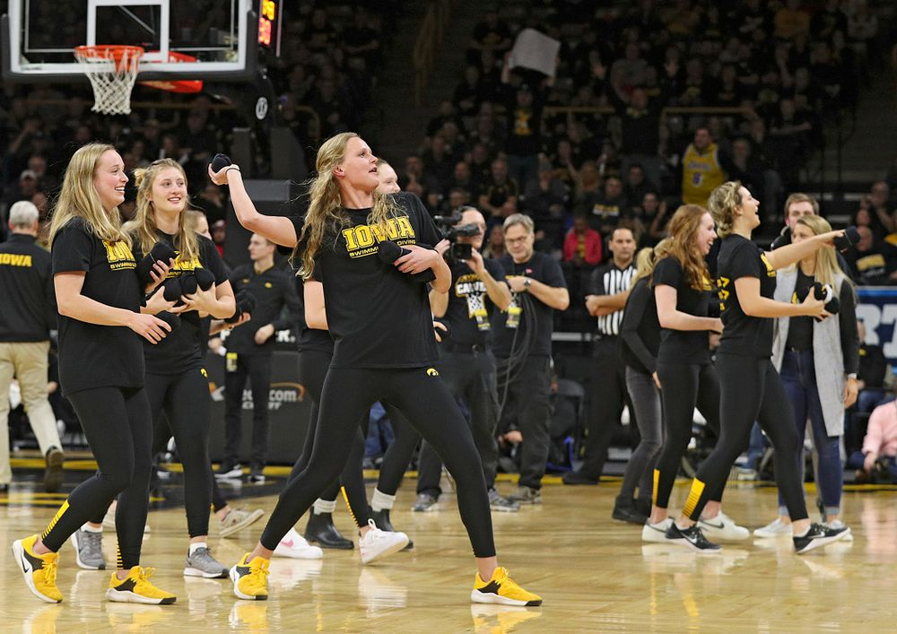 Iowa swimming and diving student-athletes throw t-shirts into the crowd during a timeout in the first half of their game at Carver-Hawkeye Arena in Iowa City on Monday, January 27, 2020. (Stephen Mally/hawkeyesports.com)