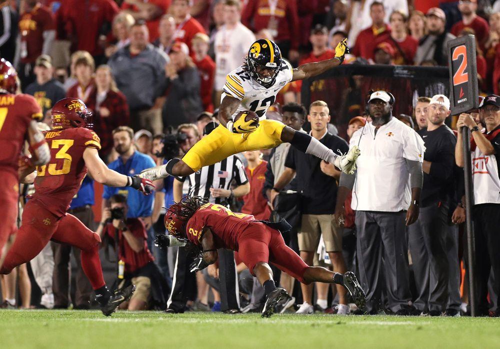Iowa Hawkeyes wide receiver Brandon Smith (12) hurdles a defender against the Iowa State Cyclones Saturday, September 14, 2019 in Ames, Iowa. (Brian Ray/hawkeyesports.com)
