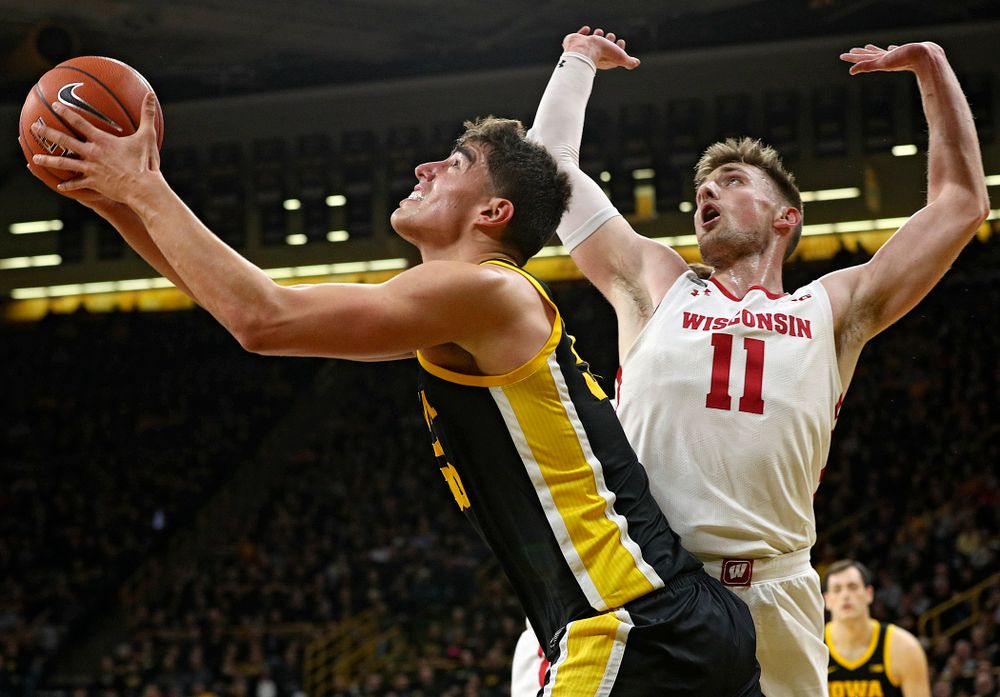 Iowa Hawkeyes center Luka Garza (55) puts up a shot around Wisconsin Badgers forward Micah Potter (11) during the first half of their game at Carver-Hawkeye Arena in Iowa City on Monday, January 27, 2020. (Stephen Mally/hawkeyesports.com)