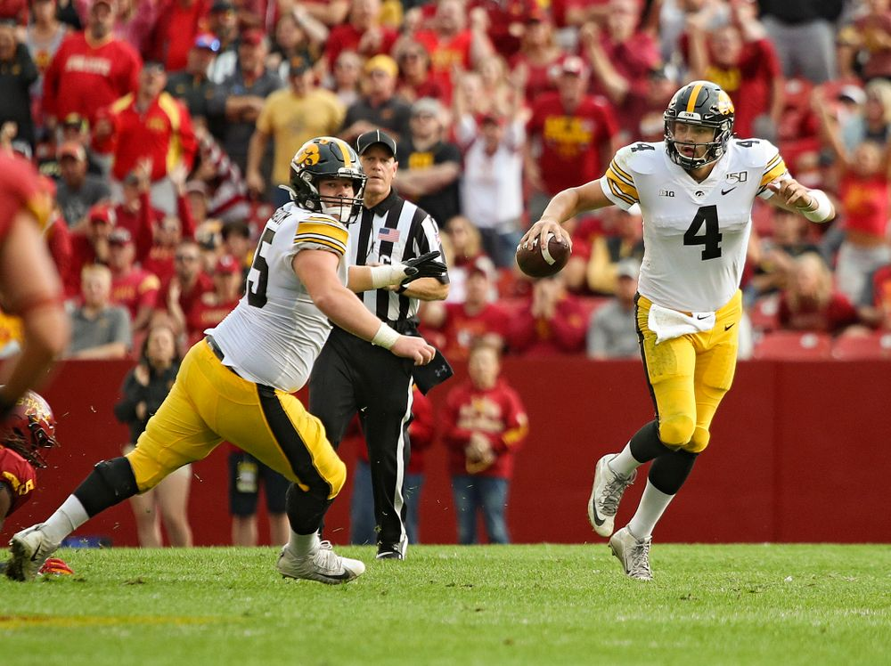 Iowa Hawkeyes quarterback Nate Stanley (4) scrambles as offensive lineman Tyler Linderbaum (65) looks to block during the second quarter of their Iowa Corn Cy-Hawk Series game at Jack Trice Stadium in Ames on Saturday, Sep 14, 2019. (Stephen Mally/hawkeyesports.com)