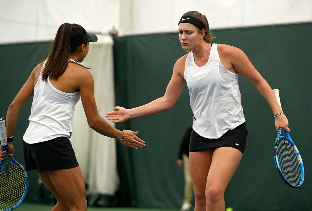 Iowa's Ashleigh Jacobs (right) celebrates with Michelle Bacalla during their doubles match at the Hawkeye Tennis and Recreation Complex in Iowa City on Sunday, February 23, 2020. (Stephen Mally/hawkeyesports.com)