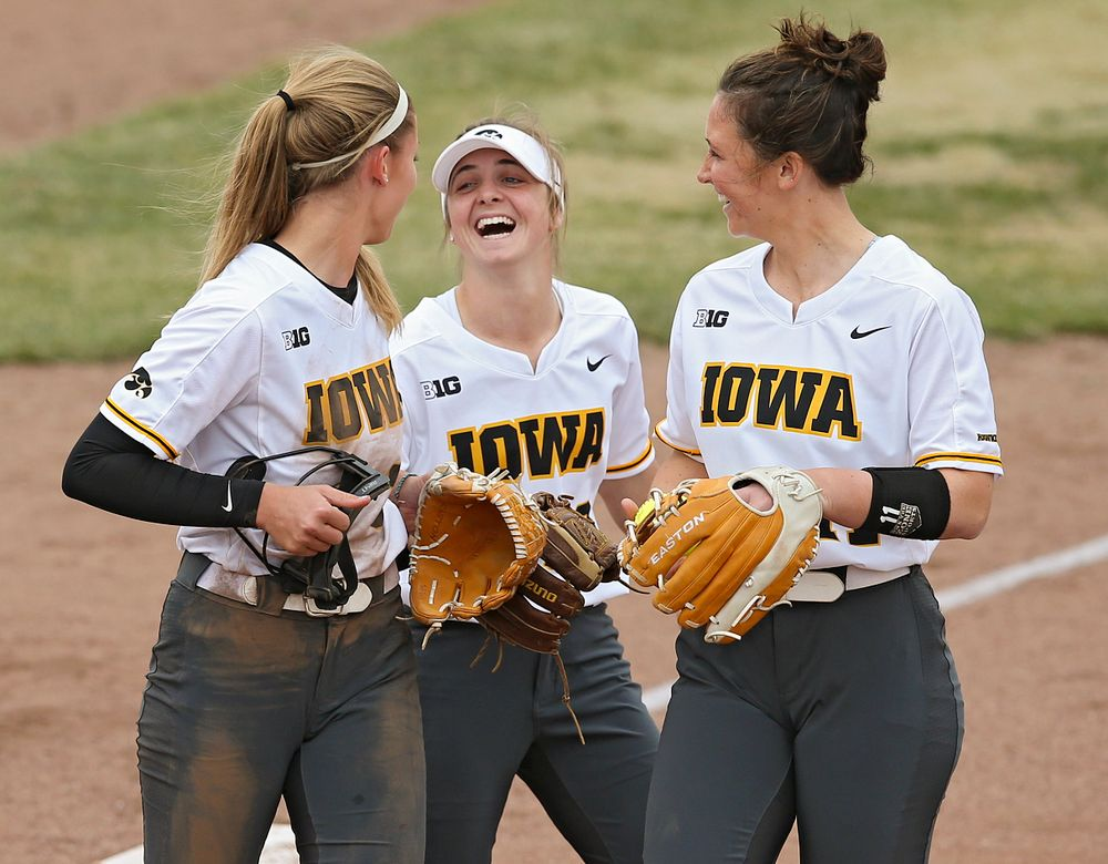 Iowa Hawkeyes Allison Doocy (from left), Hallie Ketcham (22), and Mallory Kilian (11) share a laugh during the fifth inning of their Big Ten Conference softball game at Pearl Field in Iowa City on Friday, Mar. 29, 2019. (Stephen Mally/hawkeyesports.com)