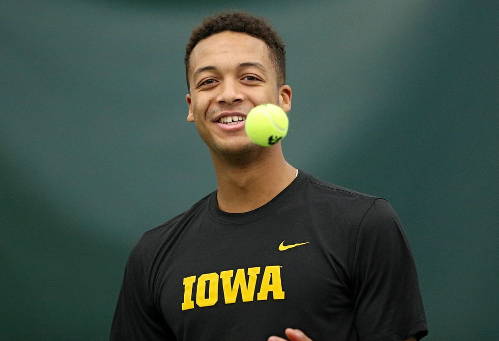 Iowa's Oliver Okonkwo tosses a ball before serving during his match against Marquette at the Hawkeye Tennis and Recreation Complex in Iowa City on Saturday, January 25, 2020. (Stephen Mally/hawkeyesports.com)