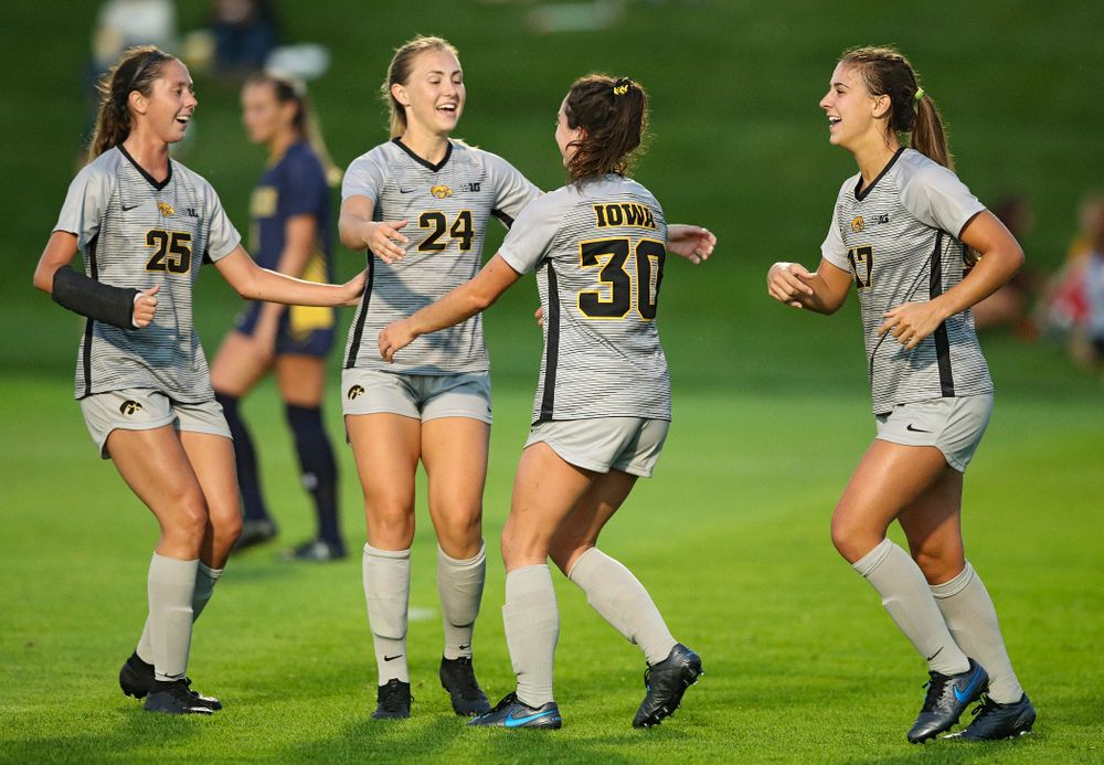 Iowa midfielder Josie Durr (25), defender Sara Wheaton (24), and defender Hannah Drkulec (17) celebrate with forward Devin Burns (30) after Burns scored a goal during the first half of their match at the Iowa Soccer Complex in Iowa City on Friday, Sep 13, 2019. (Stephen Mally/hawkeyesports.com)