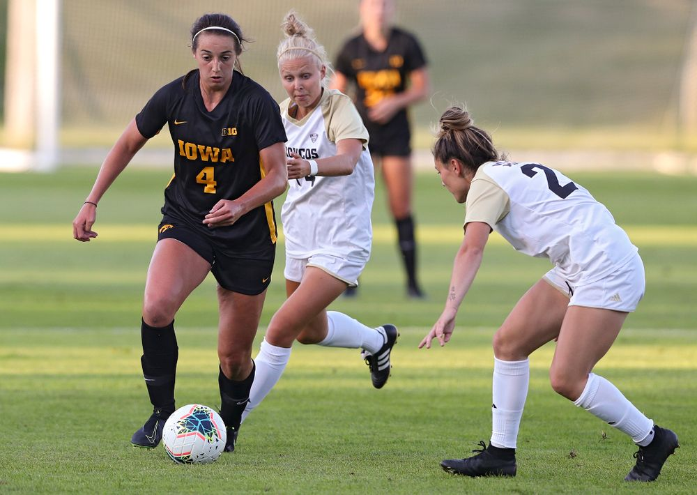 Iowa forward Kaleigh Haus (4) moves the ball around two defenders during the first half of their match against Western Michigan at the Iowa Soccer Complex in Iowa City on Thursday, Aug 22, 2019. (Stephen Mally/hawkeyesports.com)