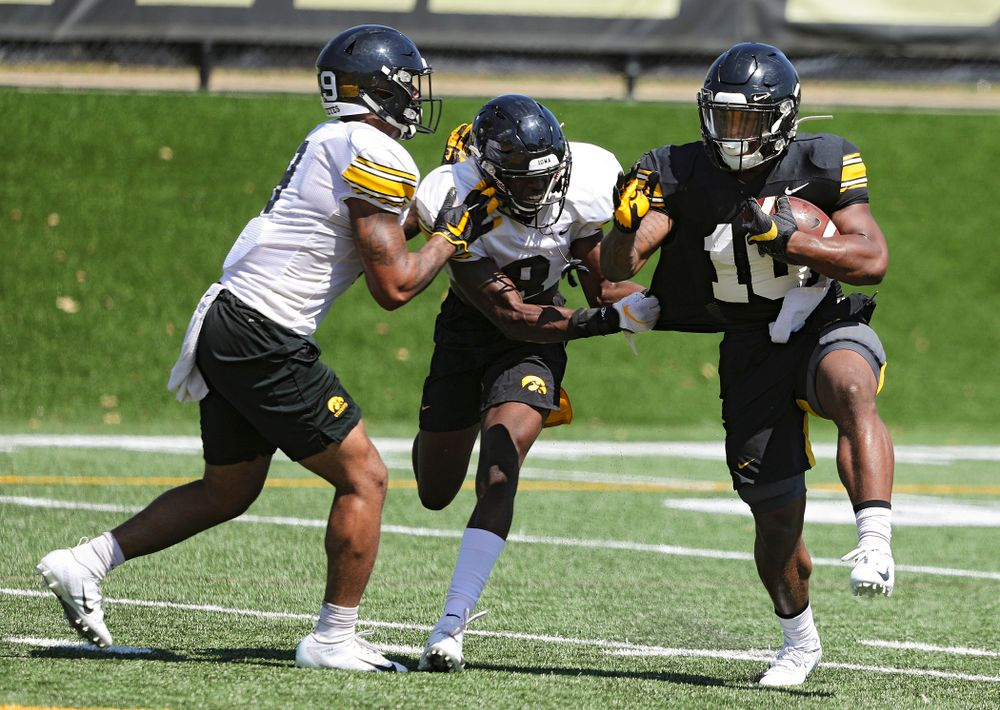 Iowa Hawkeyes defensive back Geno Stone (from left) and defensive back Matt Hankins close in on running back Mekhi Sargent (10) during Fall Camp Practice No. 7 at the Hansen Football Performance Center in Iowa City on Friday, Aug 9, 2019. (Stephen Mally/hawkeyesports.com)