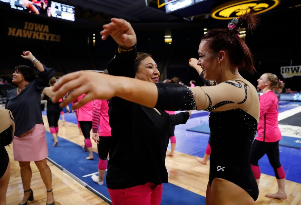 Iowa head coach Larissa Libby hugs  Maria Ortiz after her vault