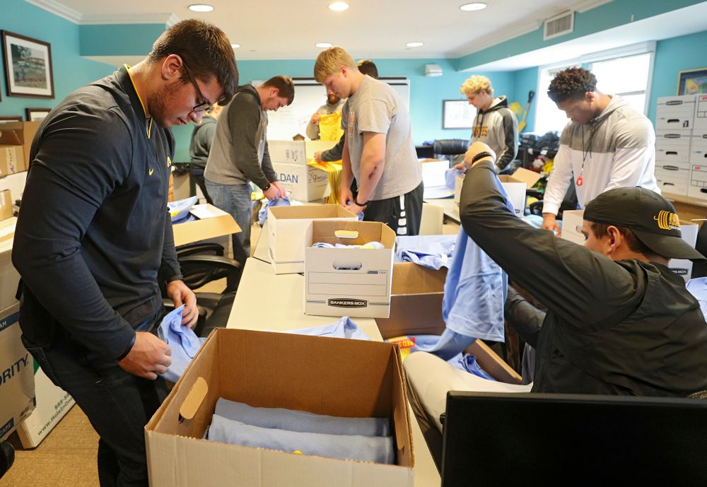 Iowa football players help fold shirts at the Ronald McDonald House for their Red Shoe Run/Walk during the 21st annual ISAAC Hawkeye Day of Caring in Iowa City on Sunday, Apr. 28, 2019. (Stephen Mally/hawkeyesports.com)