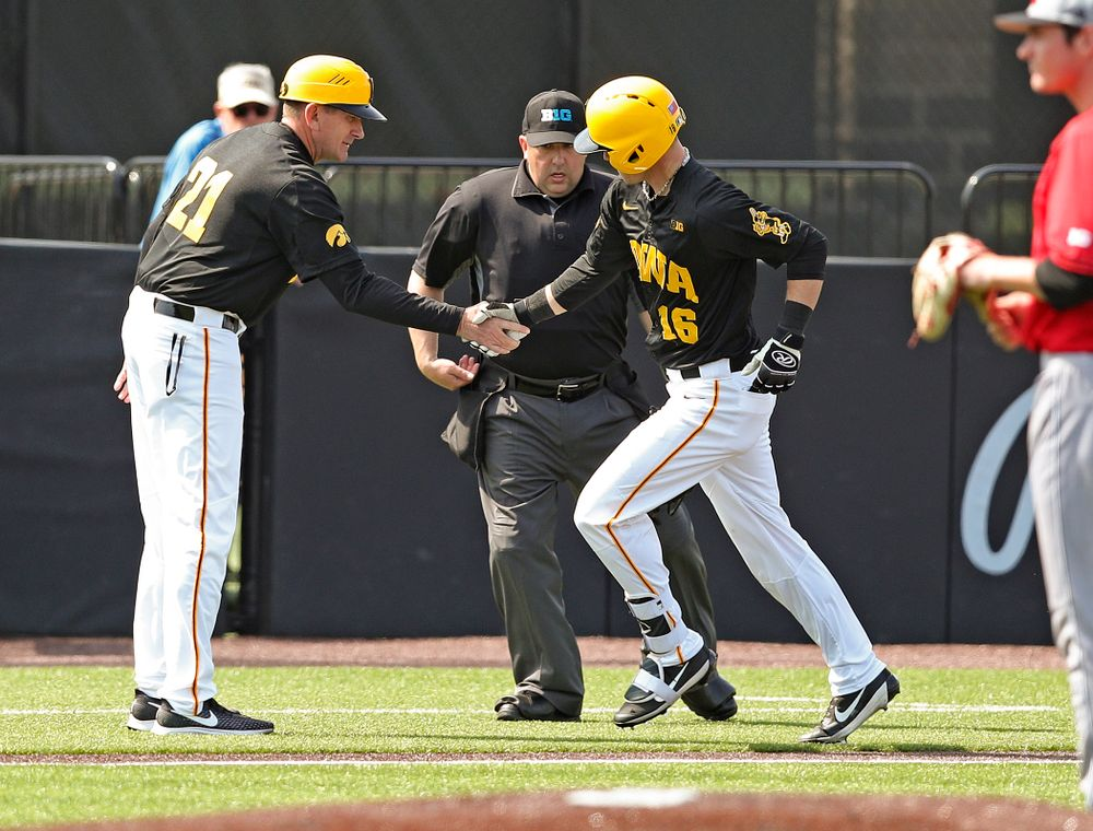 Iowa Hawkeyes head coach Rick Heller shakes hands with shortstop Tanner Wetrich (16) as he rounds the bases after hitting a solo home run during the second inning of their game against Rutgers at Duane Banks Field in Iowa City on Saturday, Apr. 6, 2019. (Stephen Mally/hawkeyesports.com)