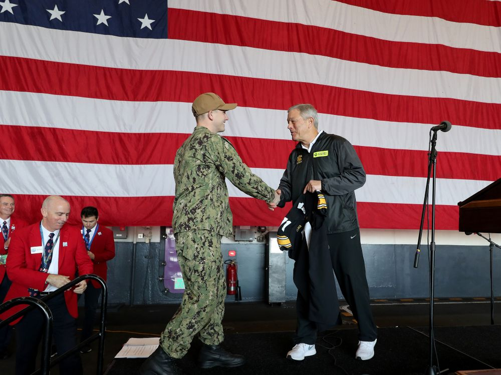 Iowa Hawkeyes head coach Kirk Ferentz presents a jersey to honorary captain Vincent OÕBrien of Bell Plaine during a tour of the USS Theodore Roosevelt (CVN-71) Tuesday, December 24, 2019 at the Naval Base Coronado. (Brian Ray/hawkeyesports.com)