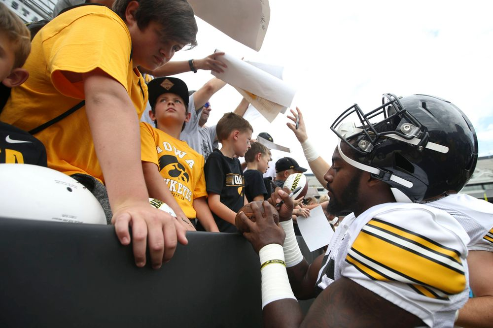 Iowa Hawkeyes linebacker Amani Jones (52) signs autographs during Kids Day at Kinnick Stadium on Saturday, August 10, 2019. (Lily Smith/hawkeyesports.com)