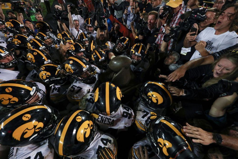 The Iowa Hawkeyes swarm to the Cy-Hawk trophy following their game against the Iowa State Cyclones Saturday, September 14, 2019 in Ames, Iowa. (Brian Ray/hawkeyesports.com)