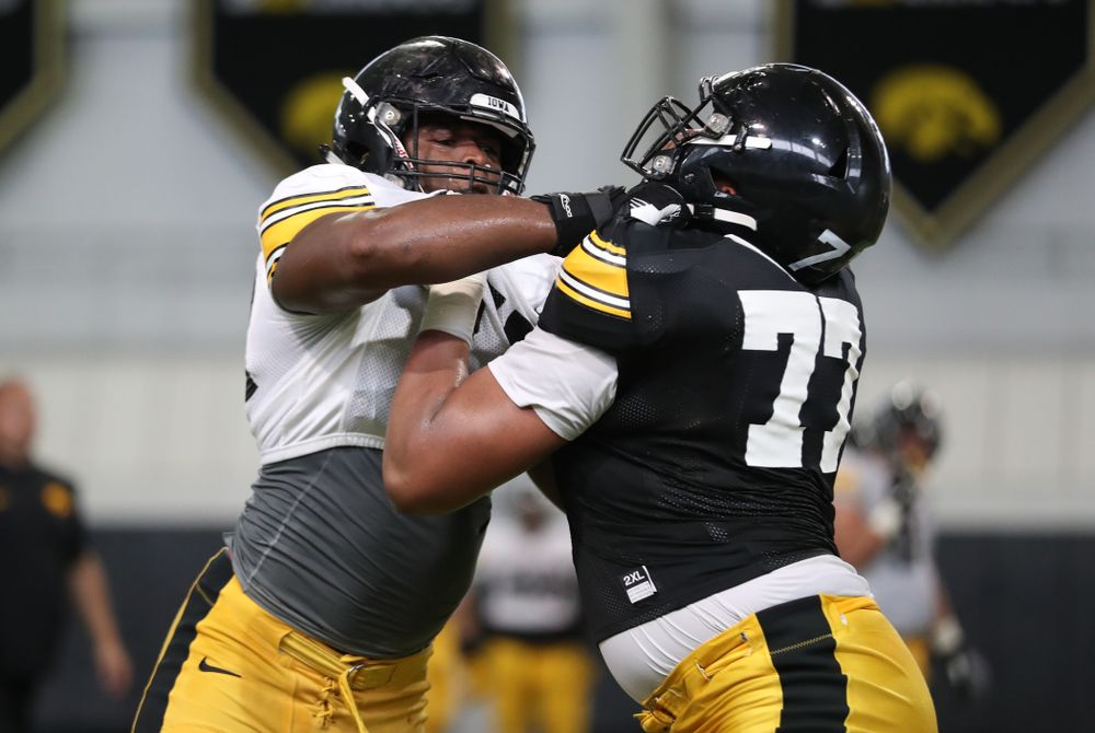 Iowa Hawkeyes defensive end Chauncey Golston (57) and offensive lineman Alaric Jackson (77)