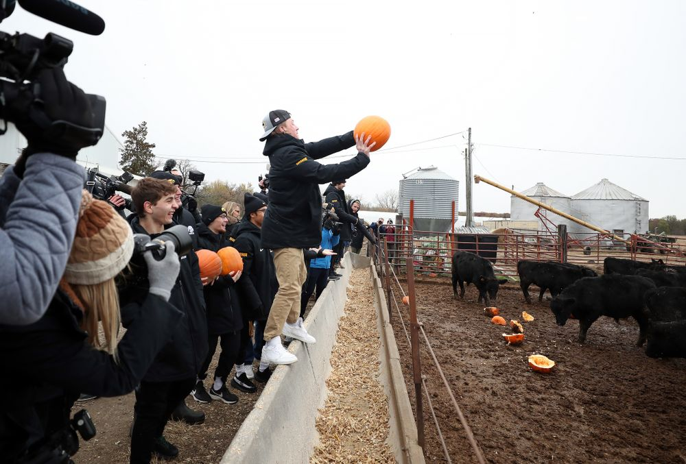 Wrestler Max Murin tosses a pumpkin into the cow pen during the teamÕs annual media day Wednesday, October 30, 2019 at Kroul Family Farms in Mount Vernon. (Brian Ray/hawkeyesports.com)
