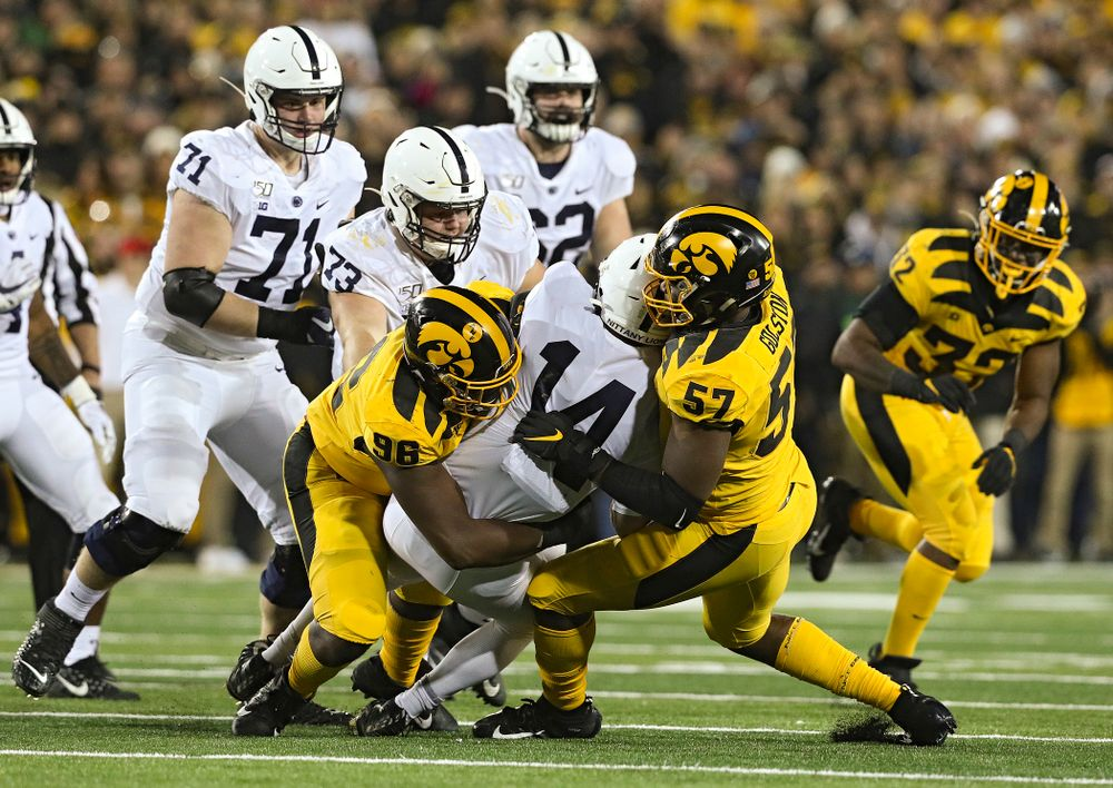 Iowa Hawkeyes defensive lineman Cedrick Lattimore (96) and defensive end Chauncey Golston (57) bring down Penn State Nittany Lions quarterback Sean Clifford (14) during the third quarter of their game at Kinnick Stadium in Iowa City on Saturday, Oct 12, 2019. (Stephen Mally/hawkeyesports.com)