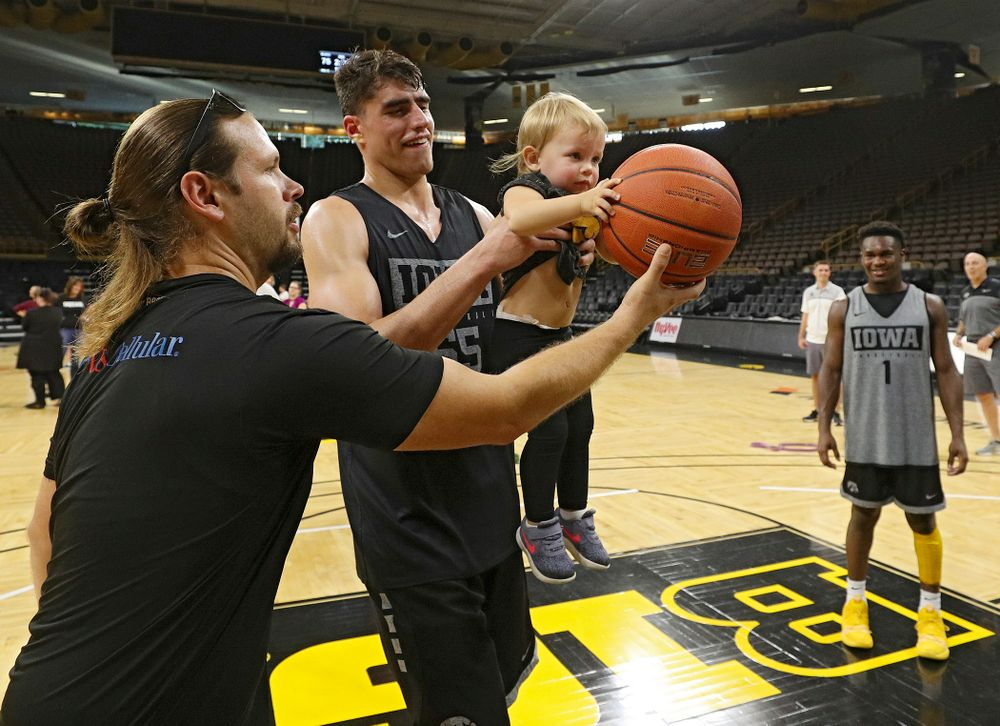 Iowa Hawkeyes center Luka Garza (55) helps a young visitor from the University of Iowa Hospitals and Clinics Adolescent and Young Adult (AYA) Cancer Program try to shoot a basket after practice at Carver-Hawkeye Arena in Iowa City on Monday, Sep 30, 2019. (Stephen Mally/hawkeyesports.com)