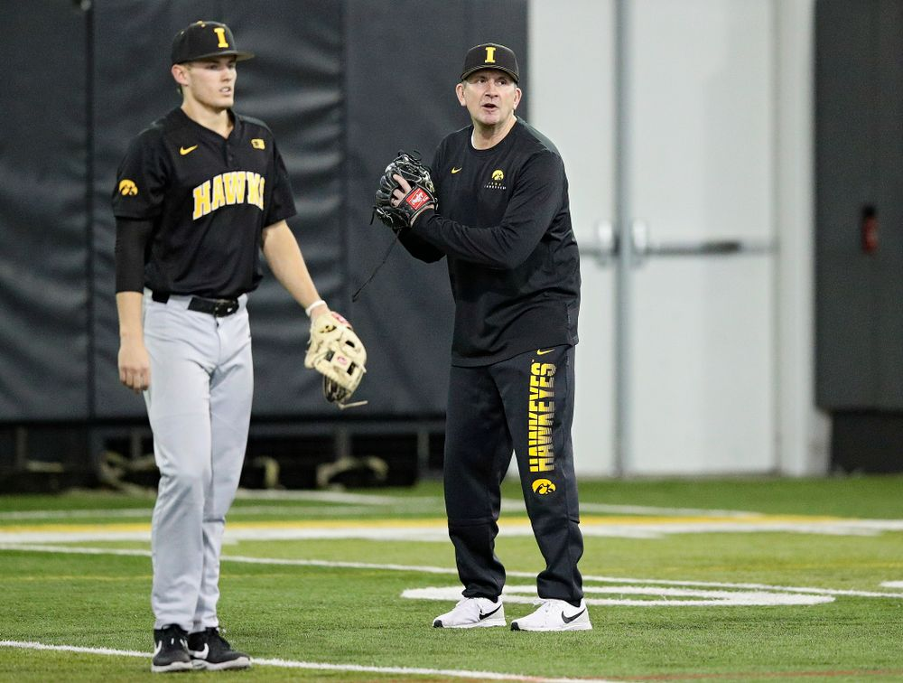 Iowa Hawkeyes head coach Rick Heller talks to his players as infielder/pitcher Dylan Nedved (17) looks on during practice at the Hansen Football Performance Center in Iowa City on Friday, January 24, 2020. (Stephen Mally/hawkeyesports.com)