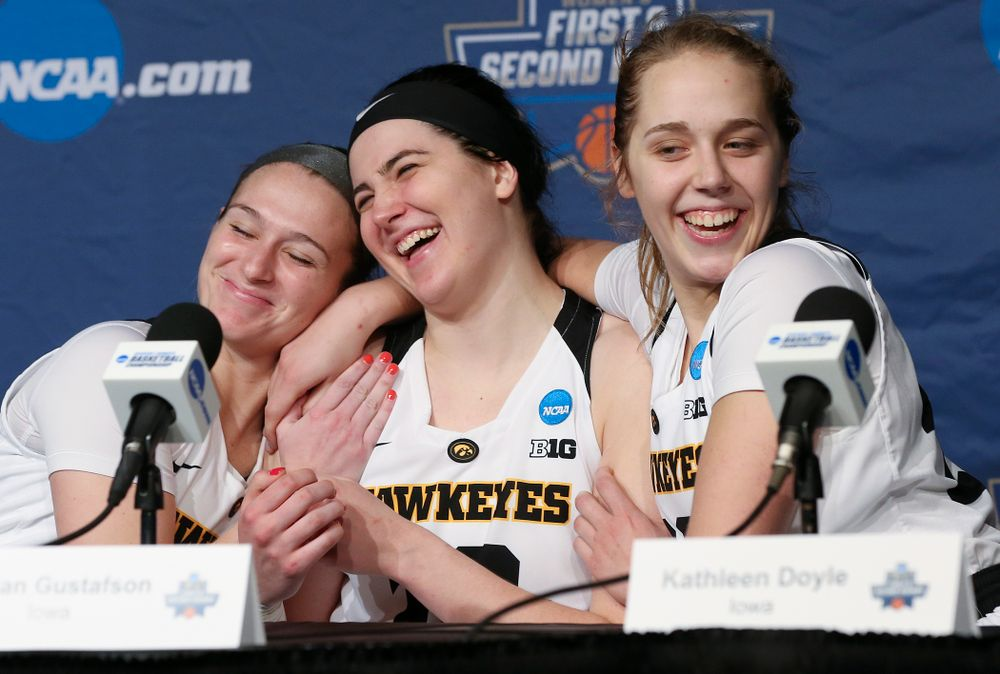 Iowa Hawkeyes guard Makenzie Meyer (left) and guard Kathleen Doyle (right) hug center Megan Gustafson (center) as she answers a question during a press conference after winning their second round game in the 2019 NCAA Women's Basketball Tournament at Carver Hawkeye Arena in Iowa City on Sunday, Mar. 24, 2019. (Stephen Mally for hawkeyesports.com)