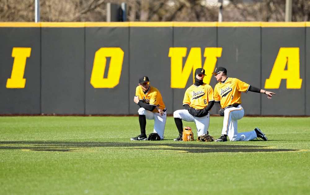 Iowa Hawkeyes outfielders Trenton Wallace (38), Justin Jenkins (6), and Ben Norman (9) talk in the outfield during a pitching change during the eighth inning against Illinois at Duane Banks Field in Iowa City on Sunday, Mar. 31, 2019. (Stephen Mally/hawkeyesports.com)