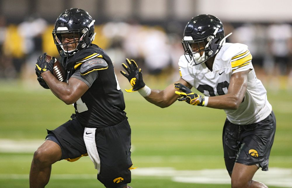 Iowa Hawkeyes running back Ivory Kelly-Martin (21) runs after pulling in a pass as defensive back Kaevon Merriweather (26) closes in during Fall Camp Practice No. 9 at the Hansen Football Performance Center in Iowa City on Monday, Aug 12, 2019. (Stephen Mally/hawkeyesports.com)