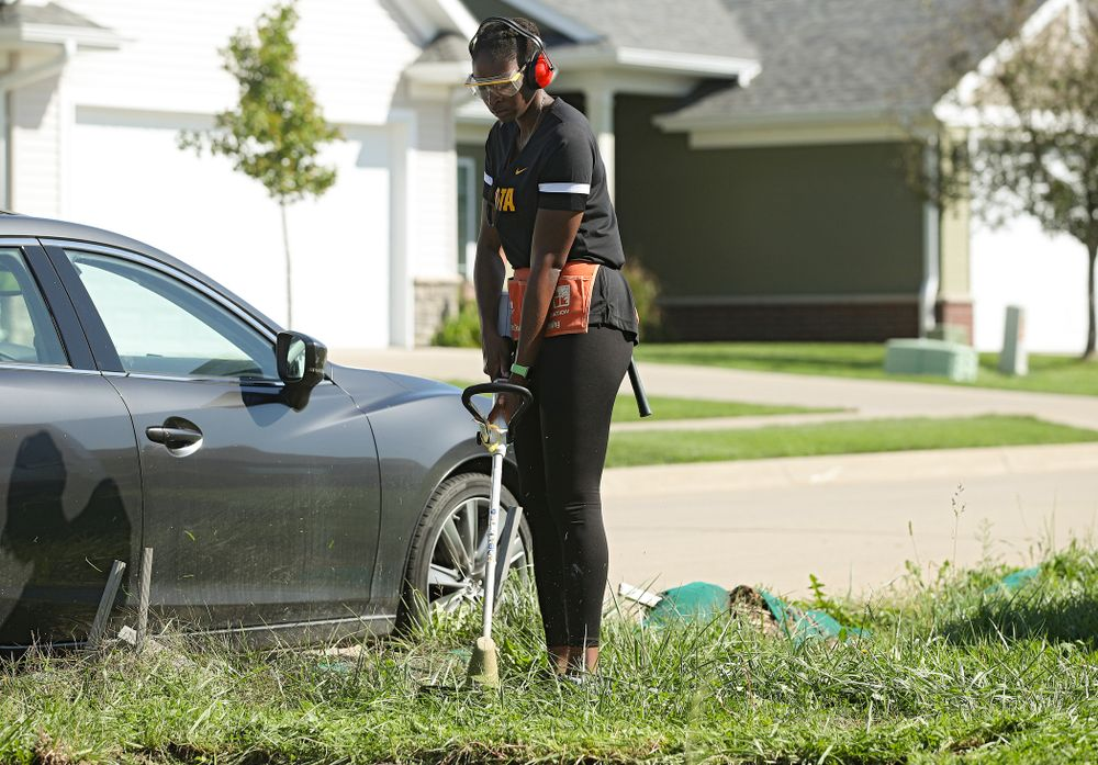 Ugo Nwaigwe, director of basketball operations, cuts down weeds with a trimmer as they work on a Habitat for Humanity Women Build project in Iowa City on Wednesday, Sep 25, 2019. (Stephen Mally/hawkeyesports.com)
