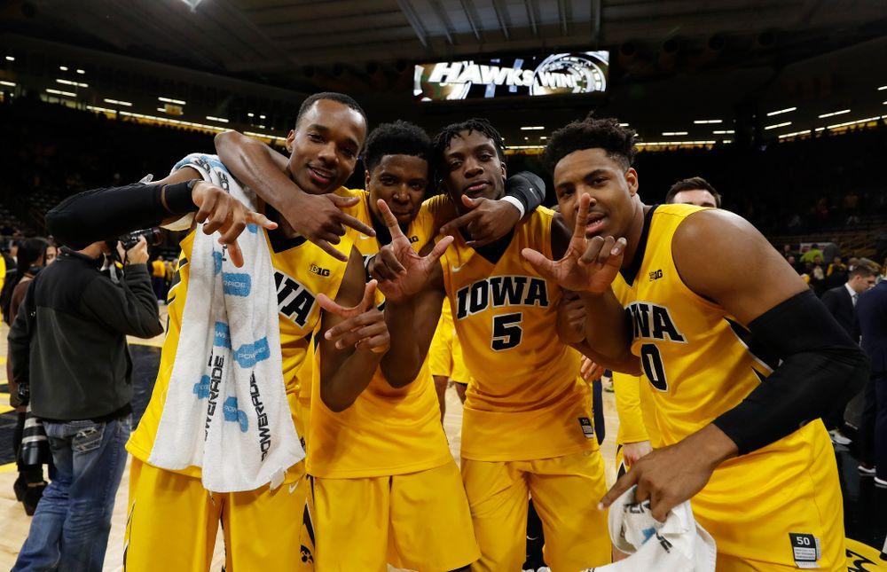 Iowa Hawkeyes guard Maishe Dailey (1), guard Isaiah Moss (4), forward Tyler Cook (5), and forward Ahmad Wagner (0)