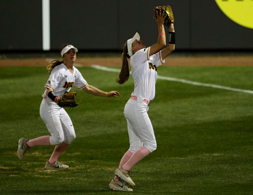 Iowa second baseman Aralee Bogar (right) pulls in a pop up for an out as right fielder Hallie Ketcham (left) looks on during the seventh inning of their game against Iowa State at Pearl Field in Iowa City on Tuesday, Apr. 9, 2019. (Stephen Mally/hawkeyesports.com)