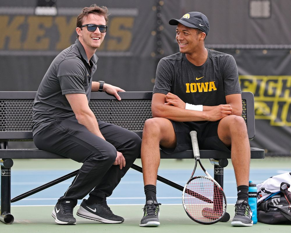 Iowa assistant coach Joey Manilla (from left) talks with Oliver Okonkwo during a match against Ohio State at the Hawkeye Tennis and Recreation Complex in Iowa City on Sunday, Apr. 7, 2019. (Stephen Mally/hawkeyesports.com)