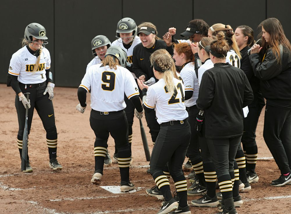 Iowa catcher Abby Lien (9) is greeted at home plate by her teammates after hitting a home run during the second inning of their game against Illinois at Pearl Field in Iowa City on Friday, Apr. 12, 2019. (Stephen Mally/hawkeyesports.com)