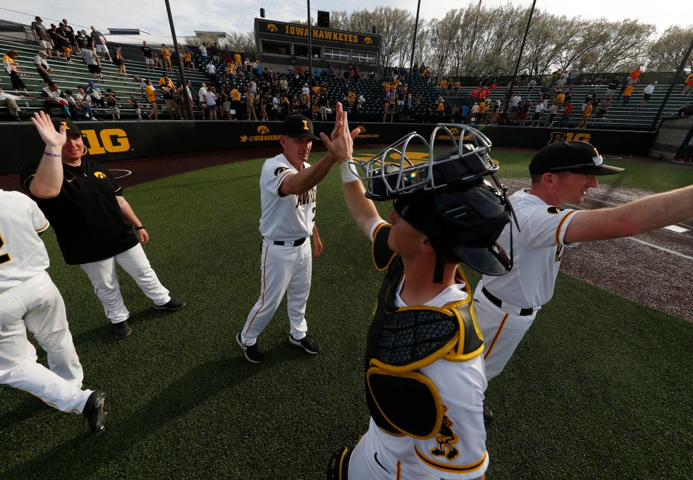 Iowa Hawkeyes head coach Rick Heller high fives catcher Tyler Cropley (5) following their win over the Oklahoma State Cowboys Saturday, May 5, 2018 at Duane Banks Field. (Brian Ray/hawkeyesports.com)