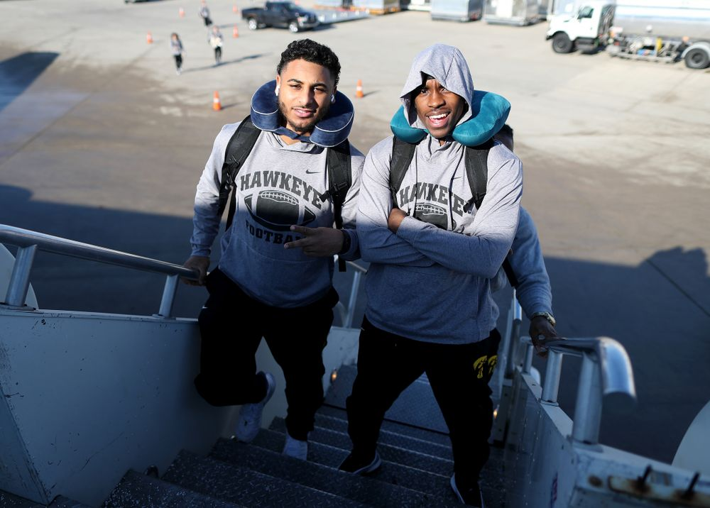 Iowa Hawkeyes defensive back Geno Stone (9) and defensive back Michael Ojemudia (11) board the team plane at the Eastern Iowa Airport Saturday, December 21, 2019 on the way to San Diego, CA for the Holiday Bowl. (Brian Ray/hawkeyesports.com)