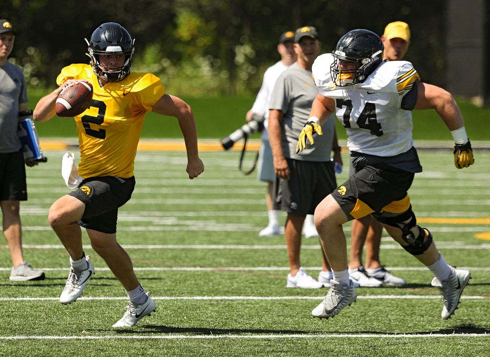 Iowa Hawkeyes quarterback Peyton Mansell (2) tries to avoid defensive lineman Austin Schulte (74) during Fall Camp Practice No. 7 at the Hansen Football Performance Center in Iowa City on Friday, Aug 9, 2019. (Stephen Mally/hawkeyesports.com)