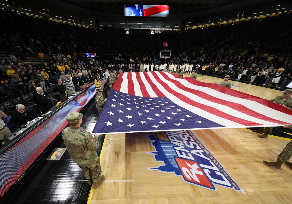 Service members stretch out a large American flag before the Iowa Hawkeyes game against UW Green Bay Sunday, November 11, 2018 at Carver-Hawkeye Arena. (Brian Ray/hawkeyesports.com)