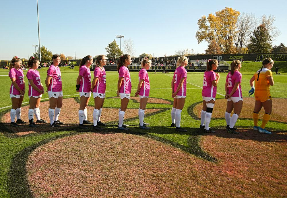 Iowa defender Riley Burns (33), forward Devin Burns (30), forward Samantha Tawharu (27), midfielder Josie Durr (25), defender Sara Wheaton (24), defender Hannah Drkulec (17), midfielder/defender Natalie Winters (10), defender Samantha Cary (9), midfielder Isabella Blackman (6), defender Riley Whitaker (5), and goalkeeper Claire Graves (1) stand for the National Anthem before their match at the Iowa Soccer Complex in Iowa City on Sunday, Oct 27, 2019. (Stephen Mally/hawkeyesports.com)
