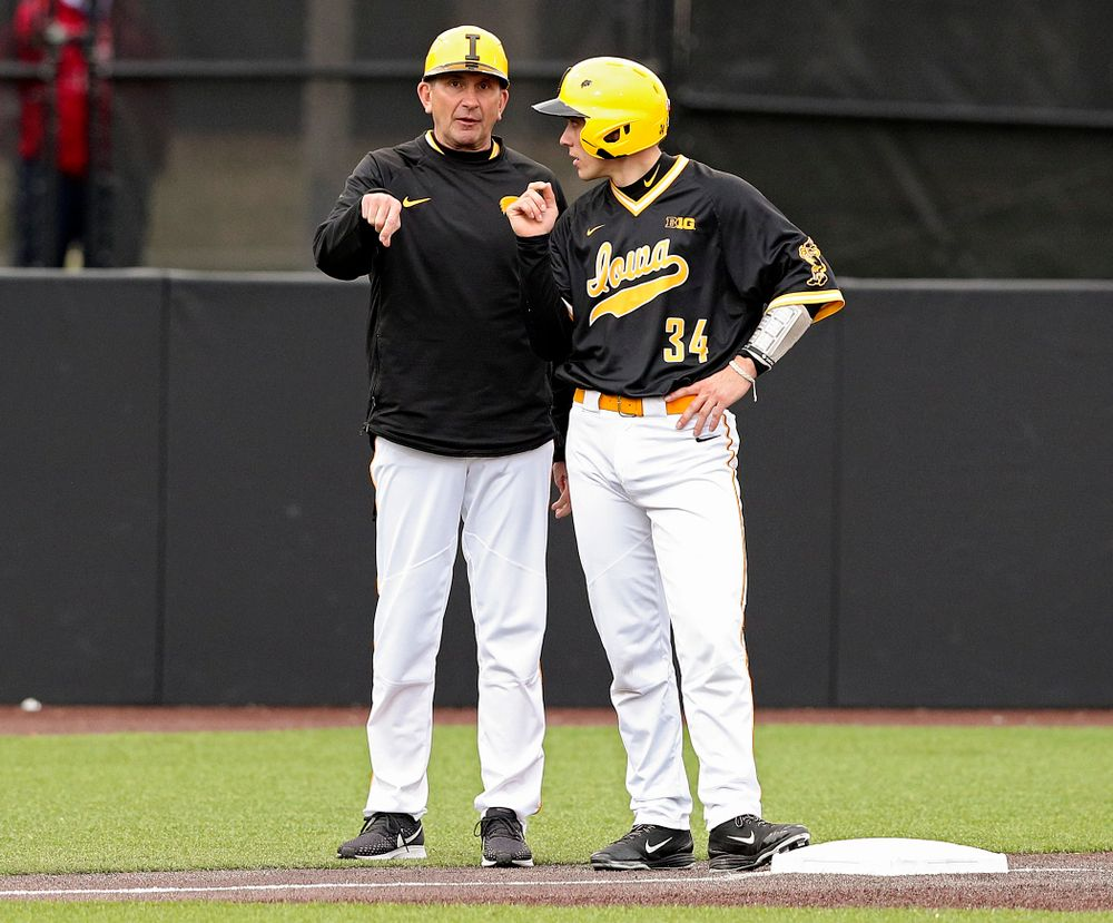 Iowa Hawkeyes head coach Rick Heller talks with catcher Austin Martin (34) on third base during the third inning of their game against Illinois State at Duane Banks Field in Iowa City on Wednesday, Apr. 3, 2019. (Stephen Mally/hawkeyesports.com)