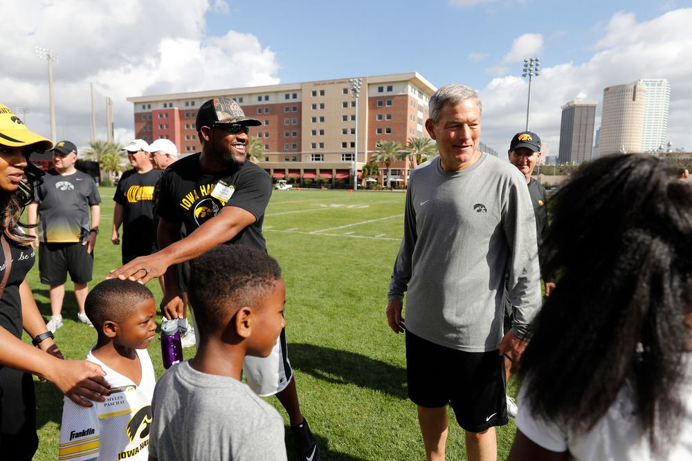 Head coach Kirk Ferentz talks with former player Marcus Paschal