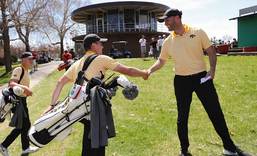 Iowa's Matthew Walker (from left) shakes hands with head coach Tyler Stith after finishing his round during the third round of the Hawkeye Invitational at Finkbine Golf Course in Iowa City on Sunday, Apr. 21, 2019. (Stephen Mally/hawkeyesports.com)