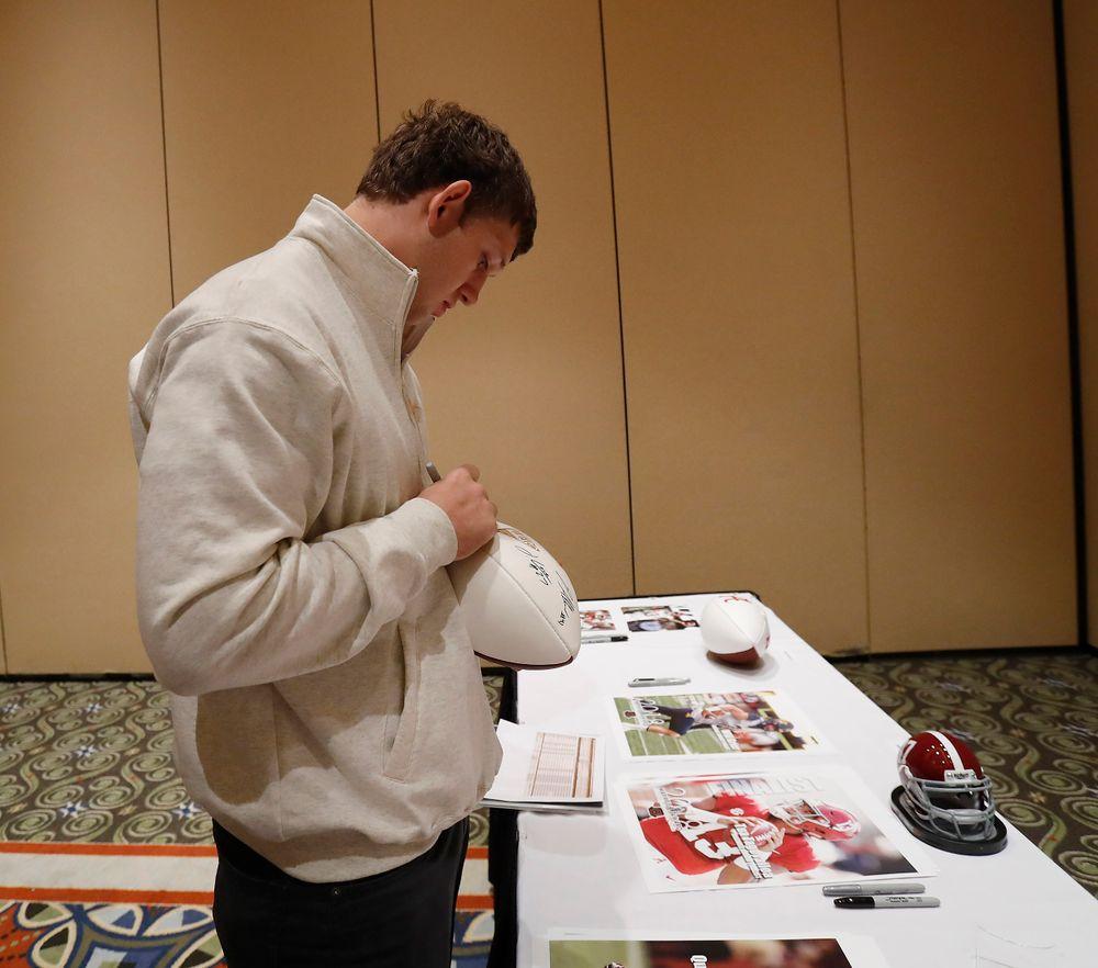 T.J. puts his signature on a football.