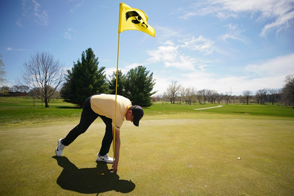 Iowa's Matthew Walker pulls out the ball he used for a hole-in-one on the fourth hole after the third round of the Hawkeye Invitational at Finkbine Golf Course in Iowa City on Sunday, Apr. 21, 2019. (Stephen Mally/hawkeyesports.com)