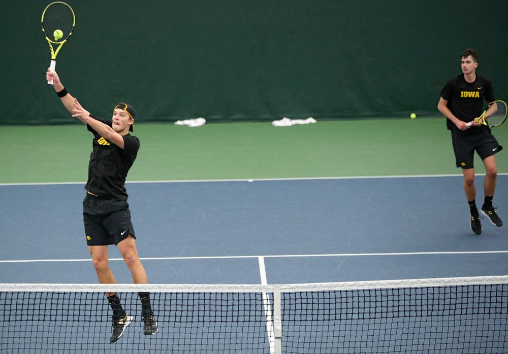 Iowa's Joe Tyler (from left) hits a shot as Matt Clegg looks on during their doubles match against Marquette at the Hawkeye Tennis and Recreation Complex in Iowa City on Saturday, January 25, 2020. (Stephen Mally/hawkeyesports.com)
