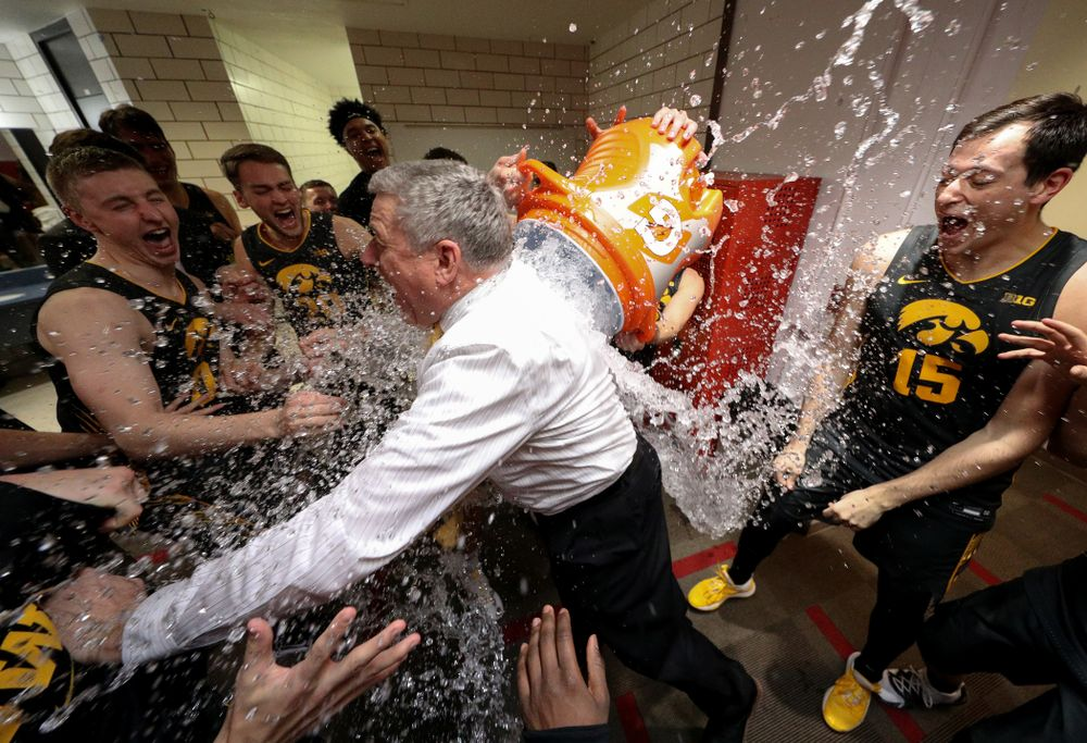 Iowa Hawkeyes assistant coach Kirk Speraw has a bucket of water dumped on him as the Iowa Hawkeyes celebrate their win against the Iowa State Cyclones Thursday, December 12, 2019 at Hilton Coliseum in Ames, Iowa(Brian Ray/hawkeyesports.com)