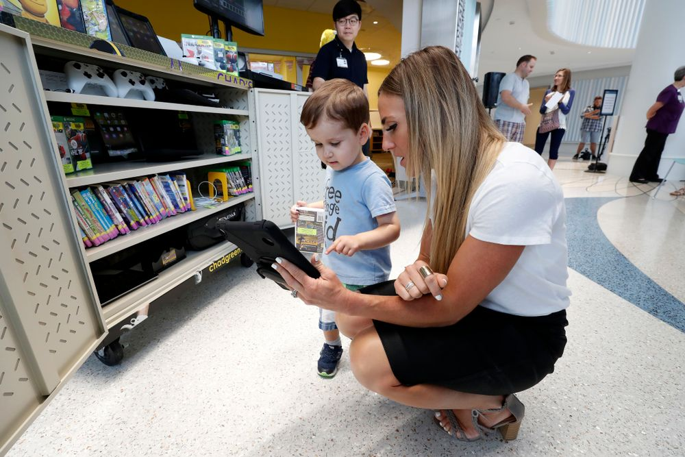 Jenni Greenway, wife of former Hawkeye Football linebacker Chad Greenway, plays with a young child after their Lead the Way Foundation unveiled their latest Greenway's Locker technology and media cabinet Friday, August 31, 2018 at the University of Iowa Stead Family Children's Hospital. Chad's Locker provides patients and their families access to notebook computers, movies and video game systems to occupy their time during their hospital stay.   (Brian Ray/hawkeyesports.com)