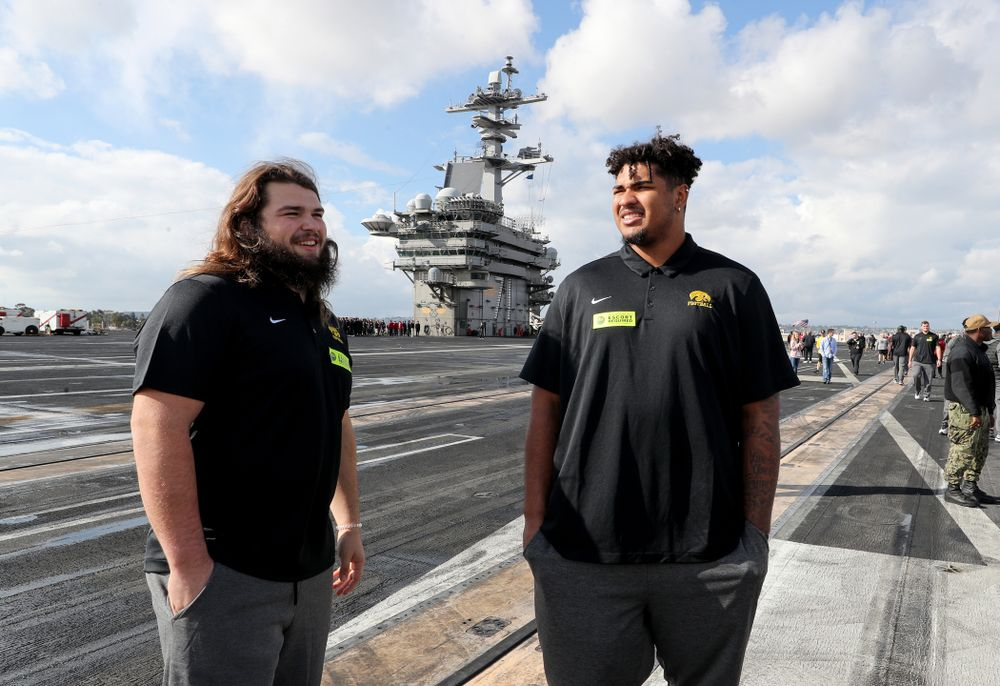 Iowa Hawkeyes offensive lineman Tristan Wirfs (74) and offensive lineman Kyler Schott (64) look around during a tour of the USS Theodore Roosevelt (CVN-71) Tuesday, December 24, 2019 at the Naval Base Coronado. (Brian Ray/hawkeyesports.com)