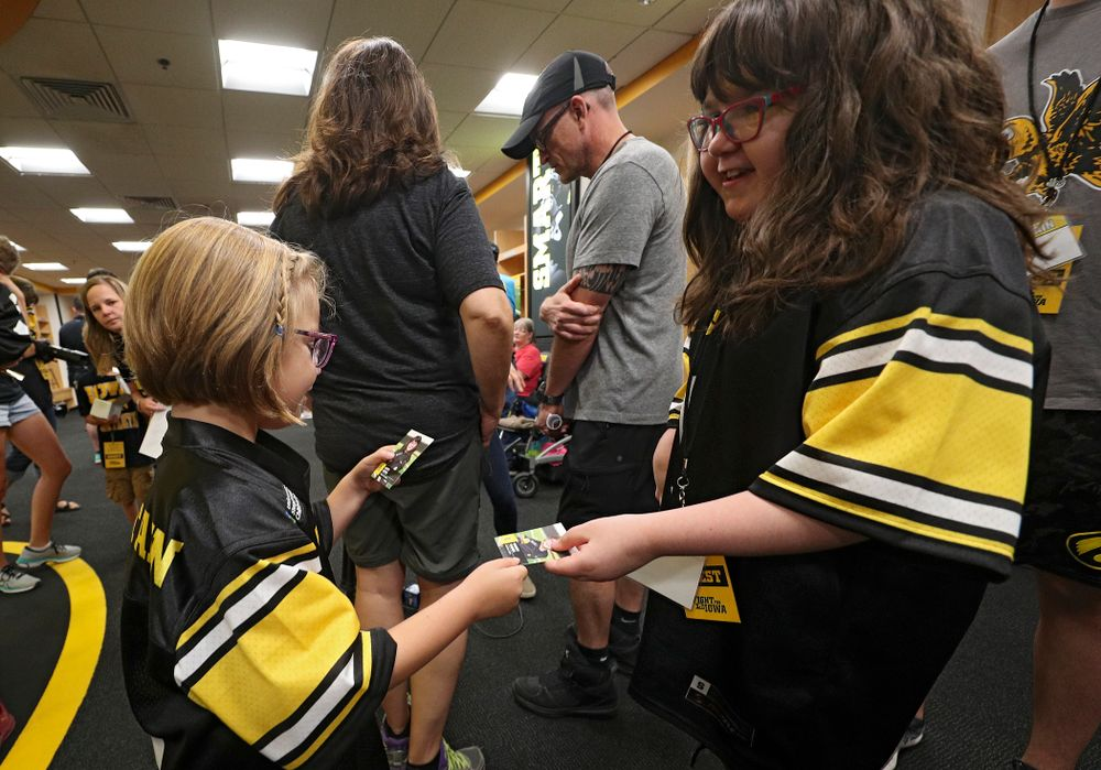 Kid Captains Gabby Yoder (from left) and Lucy Roth exchange trading cards during Kids Day at Kinnick Stadium in Iowa City on Saturday, Aug 10, 2019. (Stephen Mally/hawkeyesports.com)