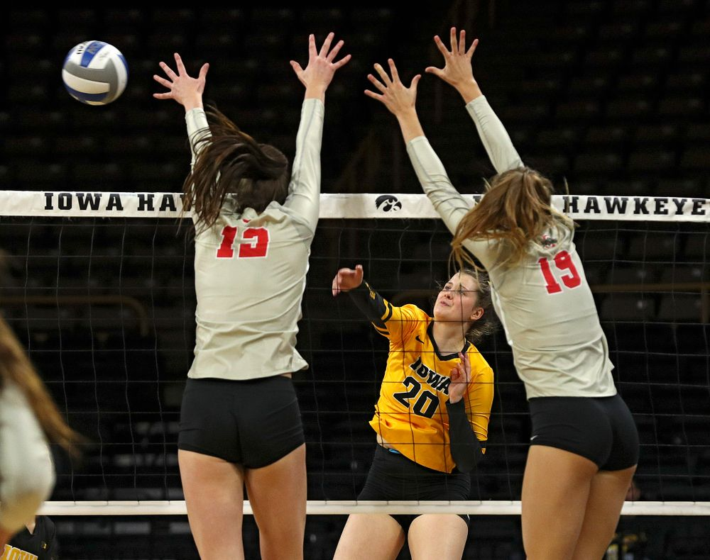 Iowa's Edina Schmidt (20) gets a kill shot over during the first set of their match at Carver-Hawkeye Arena in Iowa City on Friday, Nov 29, 2019. (Stephen Mally/hawkeyesports.com)