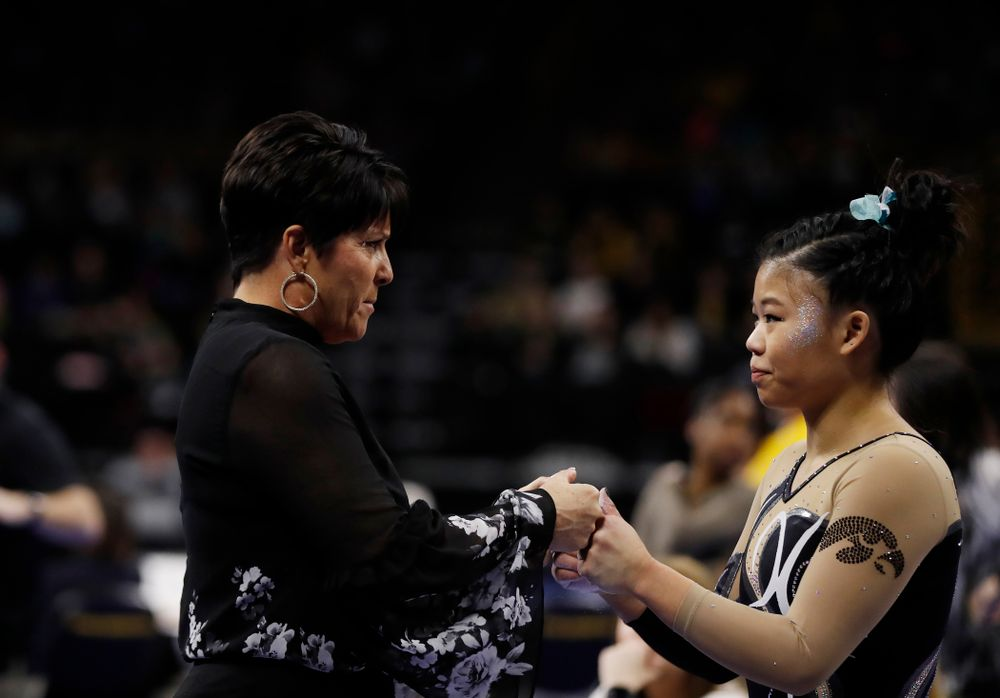 Iowa assistant coach Jennifer Green and Misty-Jade Carlson as she competes on the beam against the Nebraska Cornhuskers