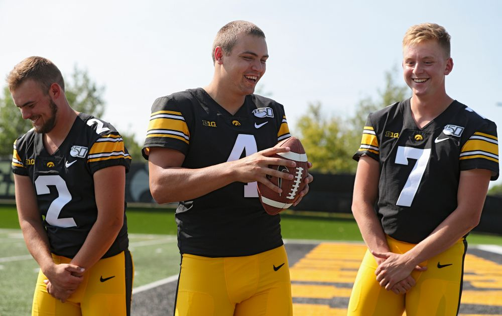 Iowa Hawkeyes quarterback Peyton Mansell (2), quarterback Nate Stanley (4), and quarterback Spencer Petras (7) laugh as they try to pose for a picture during Iowa Football Media Day at the Hansen Football Performance Center in Iowa City on Friday, Aug 9, 2019. (Stephen Mally/hawkeyesports.com)